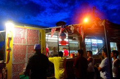 Night scene of Tacos Al Carbon take out window at dusk.